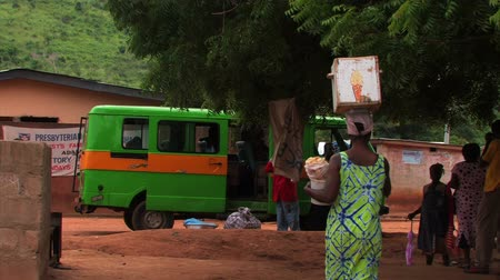dengelemek : A woman walks by with a box on her head in a village in Africa. A green van is parked in the background. Stok Video