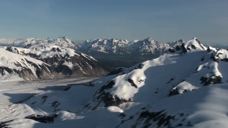 alasca : Traveling aerial view of the snow covered Coast Mountains during the day time.