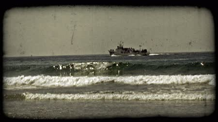 shoreline : Wide shot of tour boat or yacht full of people and trailed by birds as it travels along near the Pacific shore of California near Newport Beach. Vintage stylized video clip.