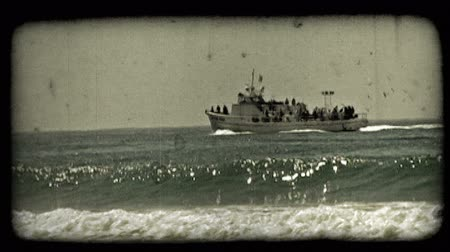 cintilante : Medium shot of tour boat or yacht full of people, and has American flag set above, and trailed behind by birds as it travels along near the Pacific shore of California near Newport Beach. Vintage stylized video clip. Stock Footage
