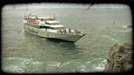 feribot : A ferry full of tourists pulls away from a rocky Italian beach. Vintage stylized video clip.