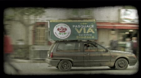 dolgok : Shot of a car with a sign on the top of it in Italy. Vintage stylized video clip. Stock mozgókép