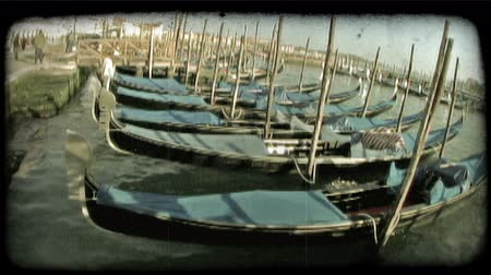 dolgok : A shot of several gondolas tied to the docks in a Venice canal. Vintage stylized video clip.