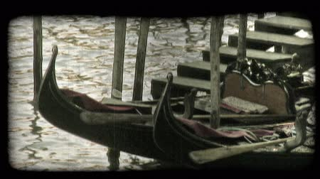 dolgok : A shot of a gondola tied to a dock in a Venice canal. Vintage stylized video clip.