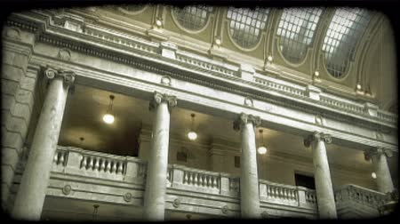 řek : Slow pan of interior of Utah Capitol, with marble columns, glass plated roof, large split staircase, intricate design, and large mural of pioneers with handcart on back wall. Vintage stylized video clip. Dostupné videozáznamy