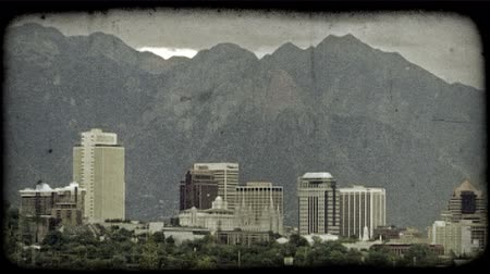 só : Static shot of Salt Lake City skyline, detailing prominant downtown buildings including the LDS Temple, with foothills and Rocky Mountains, with Mount Olympus to side, towering above in background and green trees blowing in the wind in the foreground. Vin