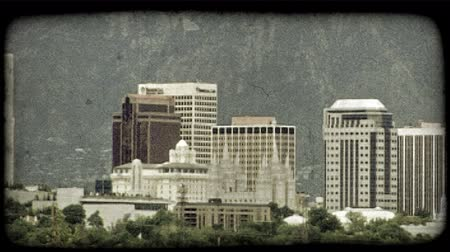 budynki : Close pan of Salt Lake City skyline, detailing prominant downtown buildings including the LDS Temple, with foothills and Rocky Mountains, with Mount Olympus to side, towering above in background and green trees blowing in the wind in the foreground. Vinta Wideo