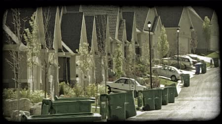 příjezdová cesta : Zoom back of suburbian street full of identically designed housing units with garages, driveways, tall street lamps, trees and bushes, and garbage bins, as car in one driveway slowly backs out of its place. Vintage stylized video clip.