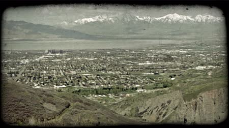 tahıllar : Still shot of populated valley basin in Utah county from high ledge, surrounded by Wasatch mountain ranges and Utah Lake in the distance. Vintage stylized video clip. Stok Video