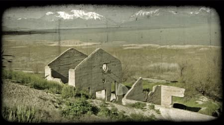 tahıllar : Old, decrepit concrete house frame near hill, with beautiful lake and snow-capped mountain vista scenery in background, with cloud formations above. Vintage stylized video clip. Stok Video