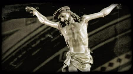 crucifixo : A lock down shot of a Jesus Christ hanging on the cross in an Italian Cathedral. Vintage stylized video clip. Stock Footage