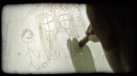 płótno : Pan from behind as a boy draws and colors in a house and stick-figure with a brown crayon on a white canvas. Vintage stylized video clip.