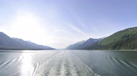 čas : Traveling time lapse view of the glassy ocean from behind a boat at the Inside Passage,surrounded by ice capped mountains with a clear blue sky in the background. Filmed at sea on June 4th,2009 in Alaska