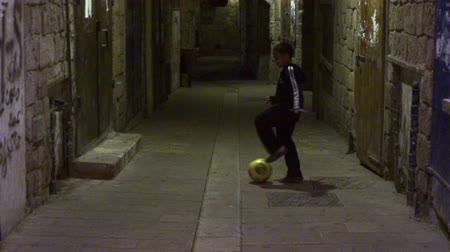 akko : Dolly shot of a boy Kicking a soccer ball in an arched alley at night in the city of Akko, Israel. Shot with the Red One digital camera at 4k 4096 x 2304 resolution. 02192011.