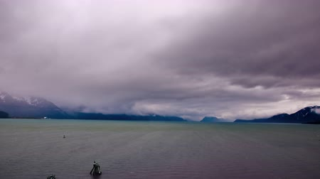 feltámadás : Stationary time-lapse of dark rolling storm clouds over the choppy water and a jagged mountain range along the horizon. Shot from the back of a cruise ship sitting in the port. Filmed on May 31st,2009 in Seward,Alaska Stock mozgókép