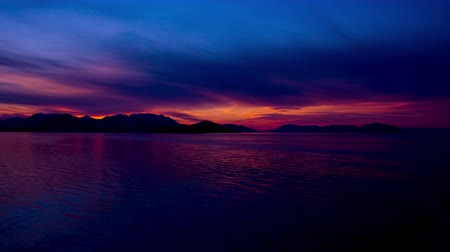 relaks : Beautiful traveling time lapse of a pink sunset behind the silhouette of a mountain range with dark blue sky background. Sunset is reflected onto the water in foreground. Shot from the back of a traveling cruise ship in the Inside Passage,Alaska Wideo