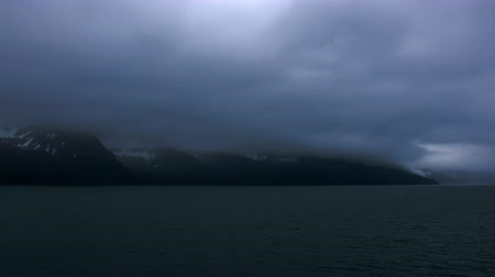 tempestade : Traveling time lapse of dark storm clouds hovering over a snow covered mountain range on the ocean near Seward,Alaska. Shot on May 31st,2009 from the front of a traveling cruise ship