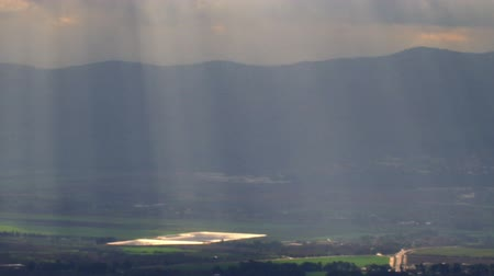 streaking : Pan of a beautiful, wide shot overlooking a valley below with awesome clouds with the sunbeams streaking across the whole valley. Taken from Nimrod Fortress in the Golan Heights, Israel. Shot with the Red One digital camera at 4k 4096 x 2304 resolution. 0