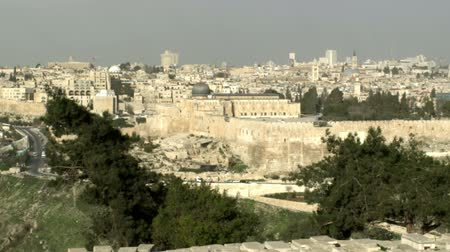 santo : Wide pan of Old Jerusalem with the Mont of Olives cemetery half in shadow and all of the Old City lit up in the early morning sun. This shot has the St. Andrews Church, the Temple Mount, Al-Aqsa Mosque, the Dome Of the Rock, the Kidron Valley, and of cour