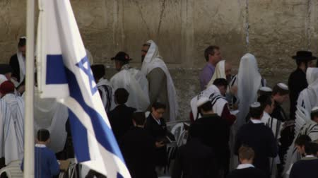 wailing : Israeli flag in the foreground and male Jews at the Western Wall Wailing Wall of the Temple Mount in Jerusalem, Israel in the background and in shadow. Shot with the Red One digital camera at 4k 4096 x 2304 resolution. 02262011