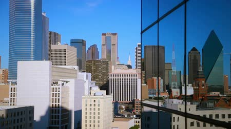 glass building : Close up footage of Dallas skyline reflection in skyscraper windows. Other buildings are visible behind the skyscraper. Filmed in Dallas, Texas. Stock Footage