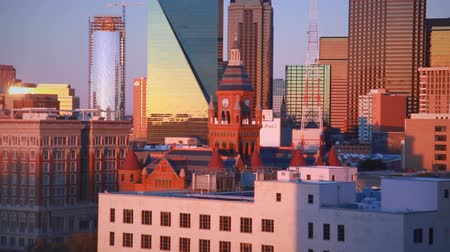 zegar : East-facing footage of the downtown skyline of Dallas during sunset. The sunset isnt visible, but its orange light reflects off the windows of the skyscrapers. A clock tower is visible among the buildings. Filmed in Dallas, Texas.