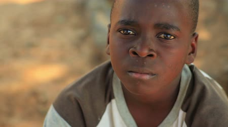 africký : Little boy looking at the camera, looks like hes about to cry. Dostupné videozáznamy