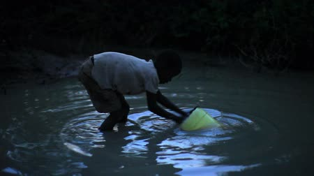coletando : Boy uses bucket to collect water from water hole at night in Africa