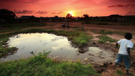 czarne : Group of boys play at village water hole at sunset in Africa Wideo