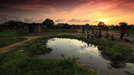 hladový : Group of boys play at village water hole at sunset in Africa Dostupné videozáznamy