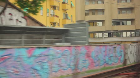 распад : A tracking shot of Italian graffiti seen from a train window. The foreground is formed of houses and walls covered with graffiti while there are some other multistorey houses in the background. A parked car also visible. Captured during daytime on May 1,