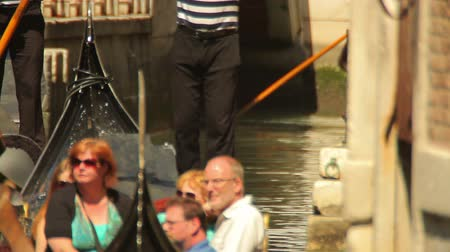 stagnant : A gondola waits, stagnant in canal waters. Passengers sit in the gondola and the gondolier stands behind them. The sun shines on all of them. Shot on May 2, 2012 in Venice, Italy.