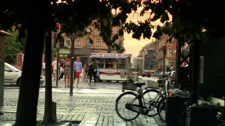 kodaň : Dolly shot of a busy street corner in Copenhagen, Denmark. Cyclists and vehicles are seen turning the corner where pedestrians are also seen walking along a small store on wheels.