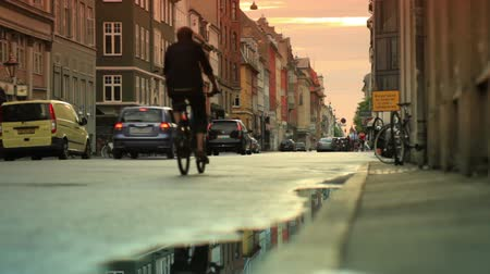 kodaň : Dolly shot of a street in Copenhagen, Denmark. The shot was taken at dusk and a car and some cyclists are seen passing by as the camera moves from left to right.