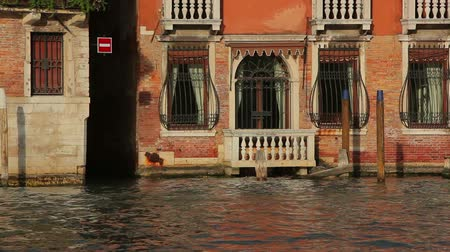 sombrio : Two boats pass by a red brick house that has bars on its windows. Captured on a canal in Venice on May 1, 2012.