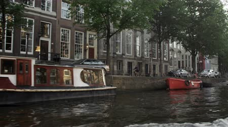 homlokzatok : A shot of a street in Amsterdam where buildings,cars and people can be seen. This was taken during the day while the videographer was aboard a boat Stock mozgókép