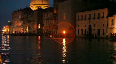 domed structure : A shot of a boat approaching a large domed structure in Venice at night.