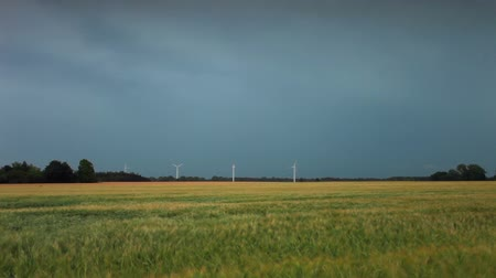 impending : Wide static shot of open field with wind turbines and an impending storm lightning flashes in the background. Filmed in Denmark.