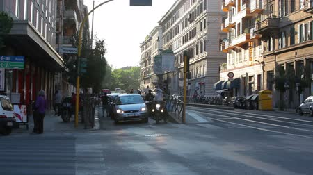 dik : Cars wait, across the road, at a stoplight, as others pass through the intersection, perpendicular to the camera. The evening sun shines on the buildings in the background of the shot. Shot on May 4, 2012 in Rome, Italy.