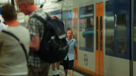 bolsa : Passengers congregate and walk along a platform in Amsterdam Central Station as a train pulls away. Filmed in Amsterdam, Holland, c. 2012