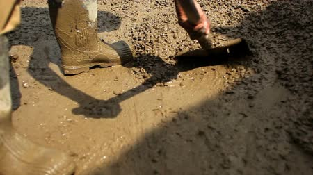 kalhoty : Close up of someone in boots using a shovel to stir and move muddy gravel. Dostupné videozáznamy