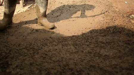 laboring : Close up of someone in boots using a shovel to stir and move muddy gravel. Stock Footage