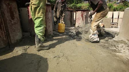 talaj : Medium shot of 3 kenyon men shoveling gravel in a pile. Filmed during the day in Kenya, Africa.