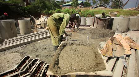 dirt : Man shoveling gravel into wheelbarrow at a construction site while other men shovel in the background. Filmed in Kenya, Africa. Stock Footage