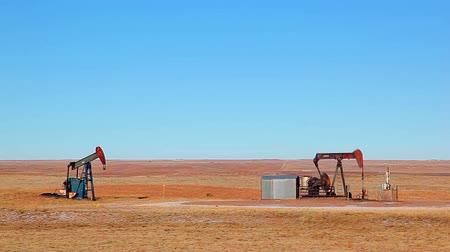 навес : Stationary shot of oil rigs in the middle of an oil field during the daytime, located in Nebraska.