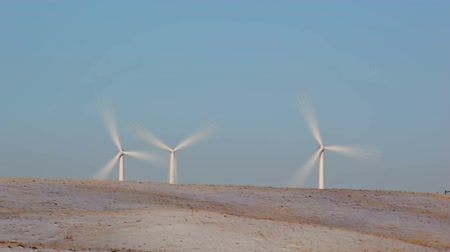 sustentável : Stationary shot of windmills in Wyoming during the daytime with a beautiful blue backdrop.
