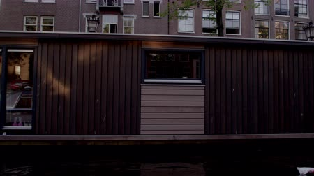 homlokzatok : Shot of houseboats and a street in Amsterdam. This was taken from a boat on the river