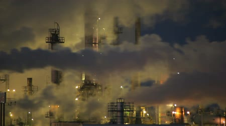 füstös : Stationary shot of factory smoke stacks during the night in Wyoming.