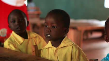küçük kız : Close up of two children sitting at a table and singing with classmates in a Kenya, Africa school.