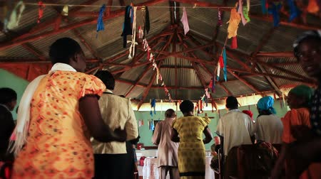 Кения : Low-angle, medium footage of people singing and dancing in the aisle and between the benches of a Christian church service in Kenya, Africa. Filmed in the aisle, behind the participants. Стоковые видеозаписи
